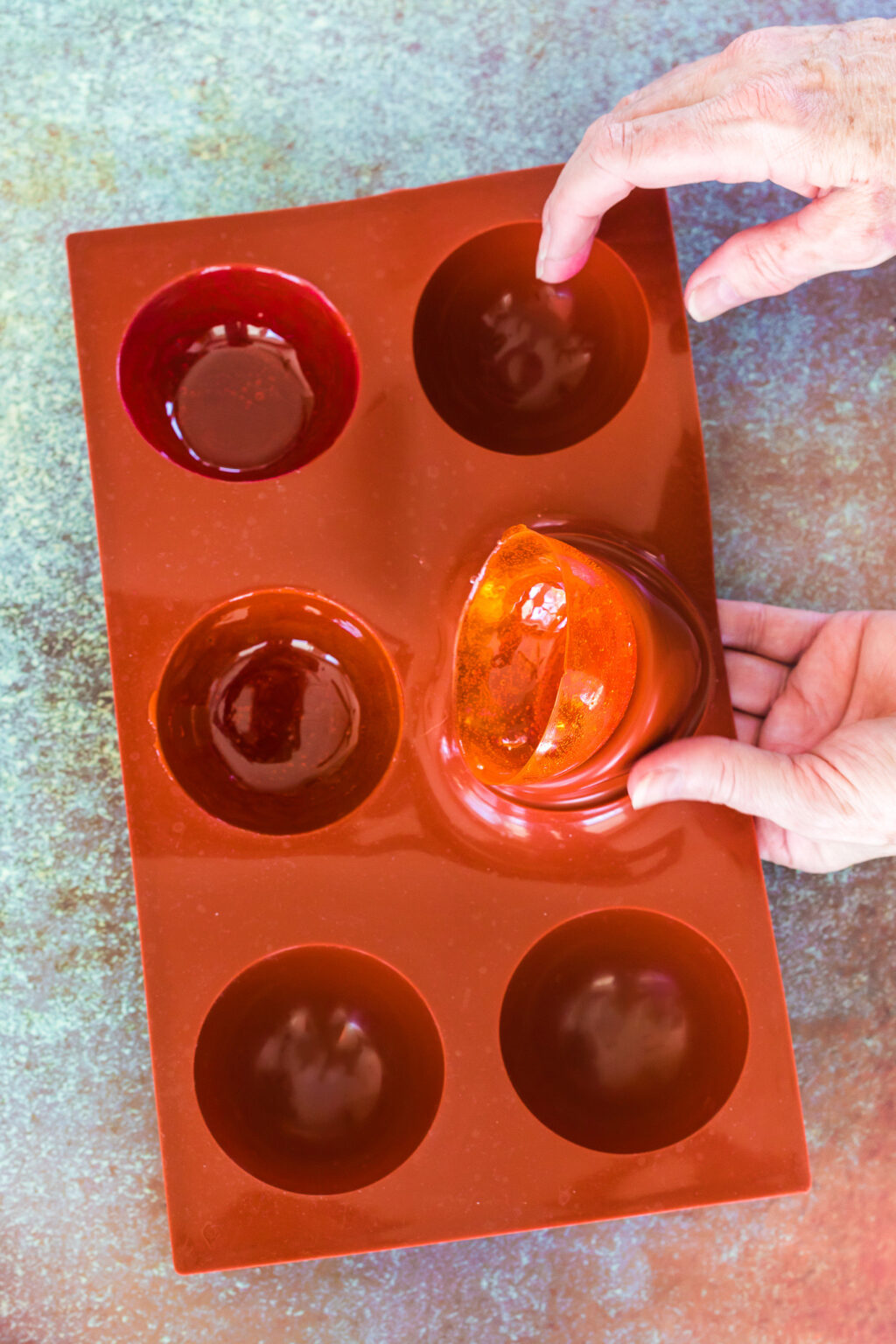 hand removing tea bomb from mold