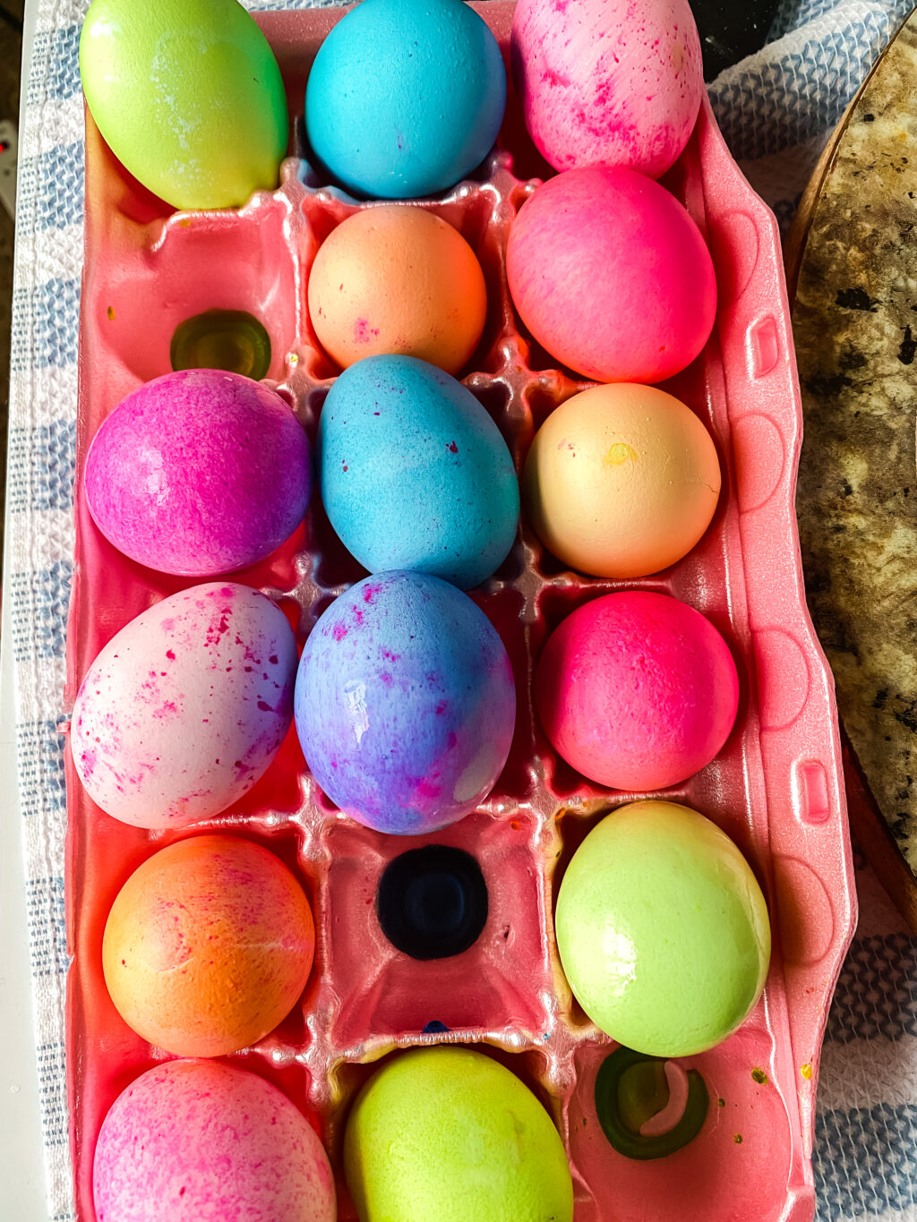 top view of brightly dyed easter eggs in egg carton