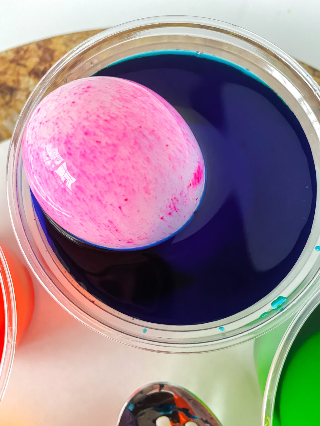 hard boiled egg being dyed in cup of food coloring