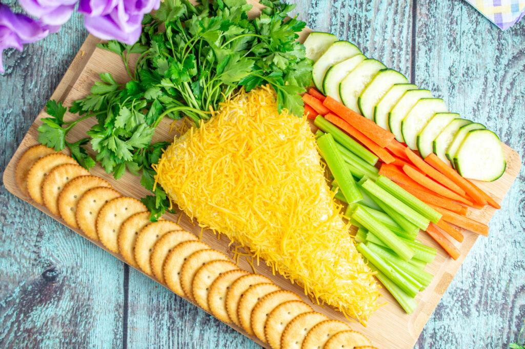 easter carrot cheese ball on cutting board with vegetables and crackers around it