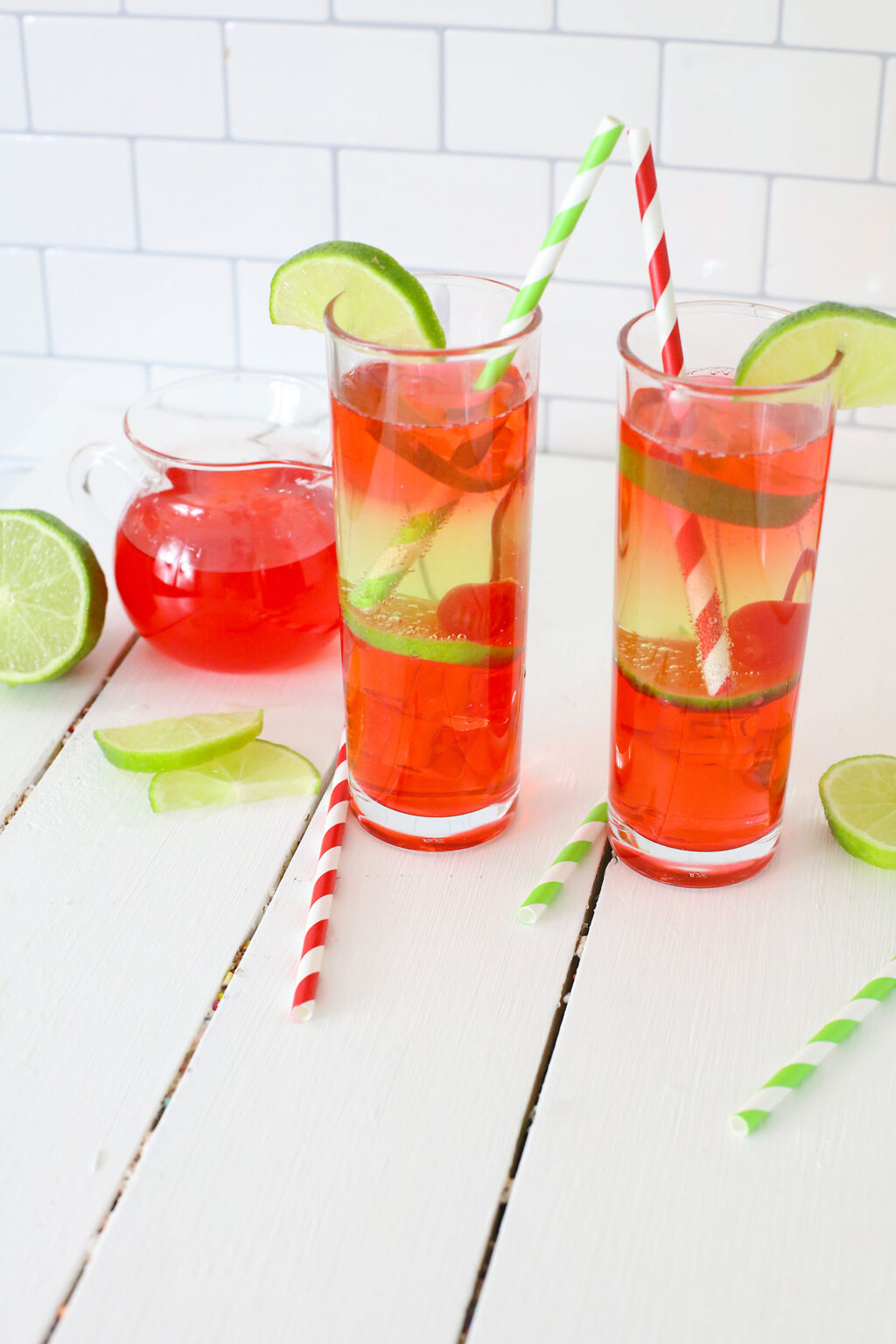 vodka cherry limeade cocktail in a tall glass with a straw
