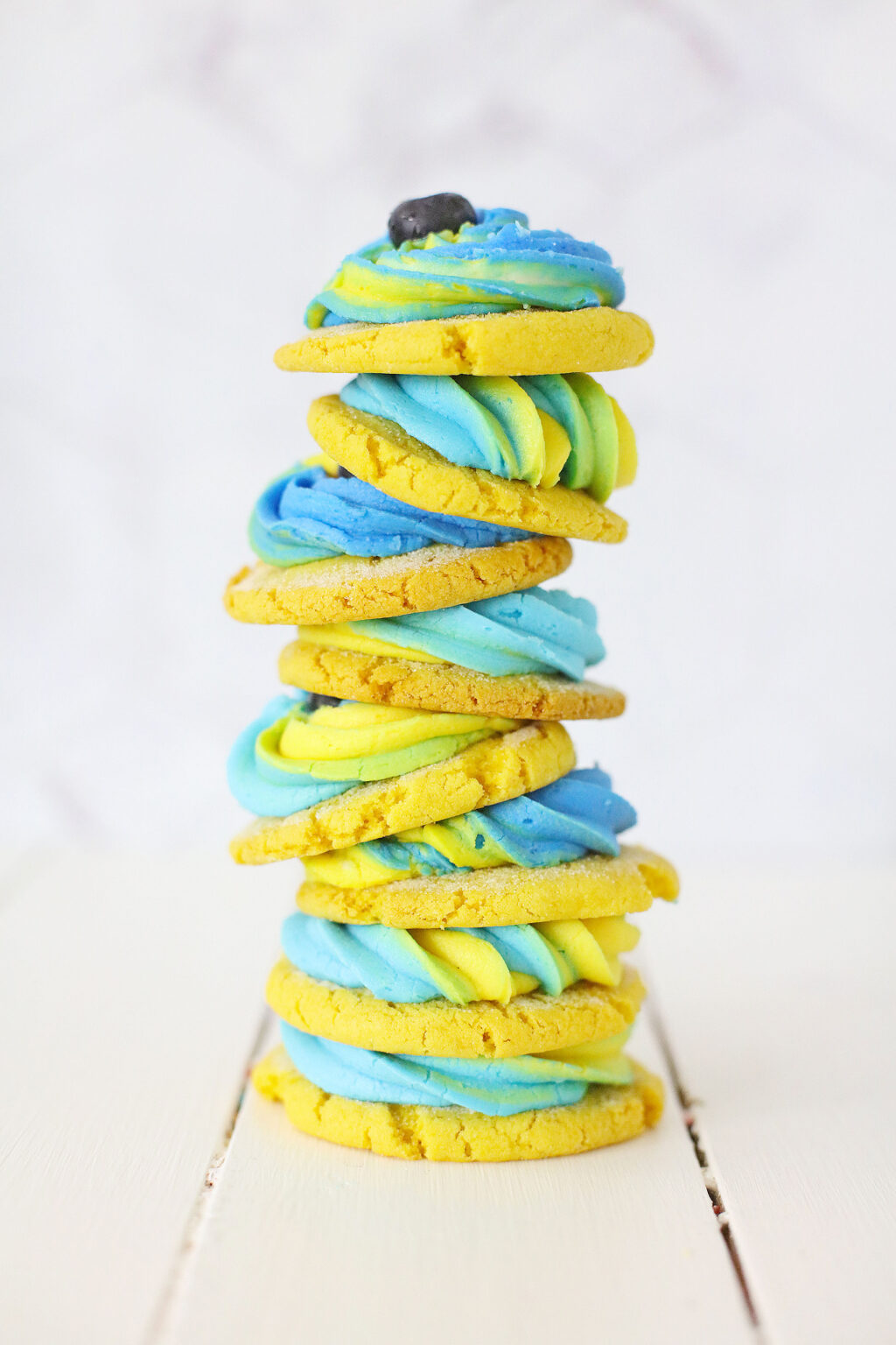 lemon blueberry cookies stacked on white wood table