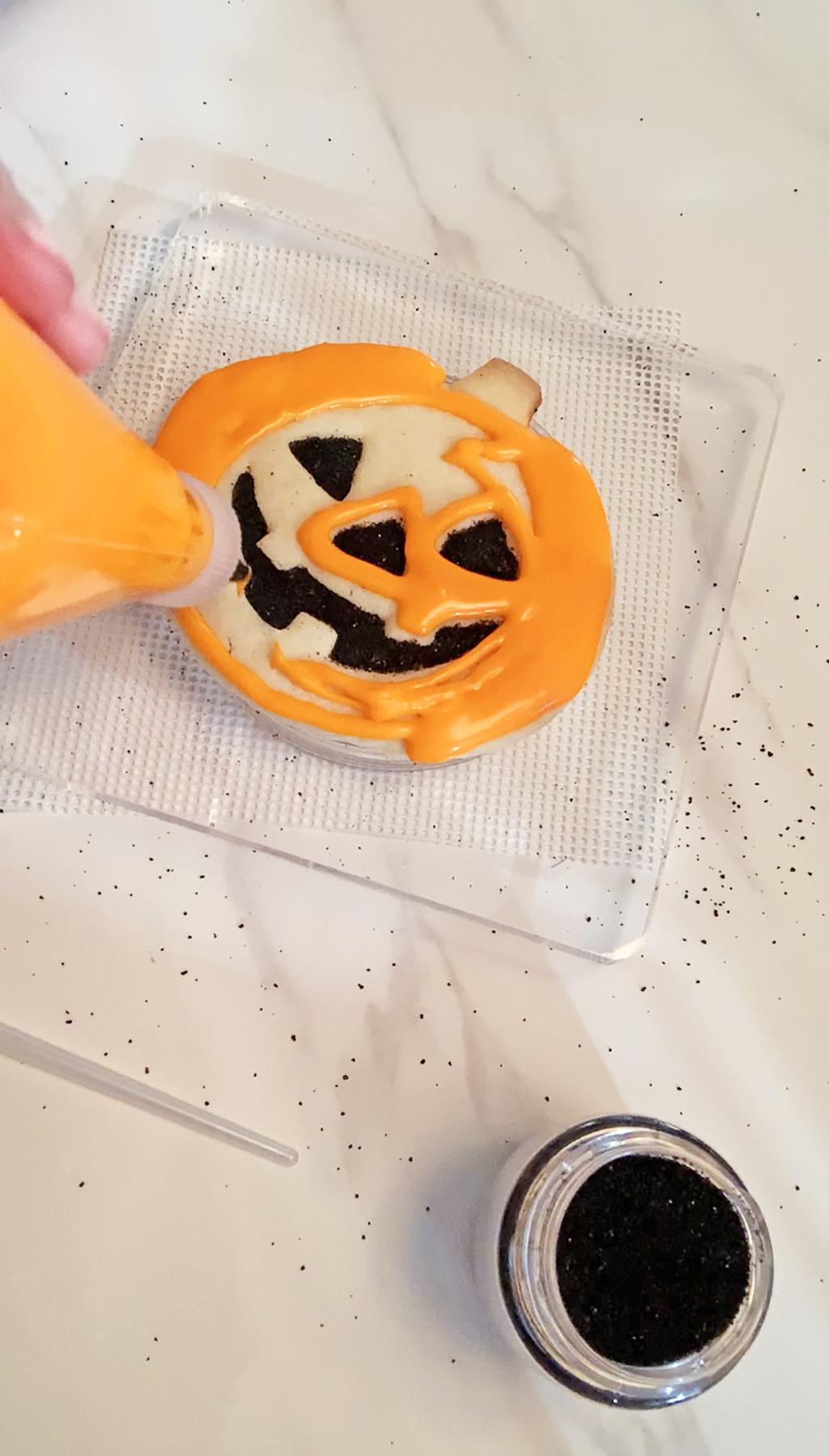 hand piping orange frosting onto baked jack o lantern cookie
