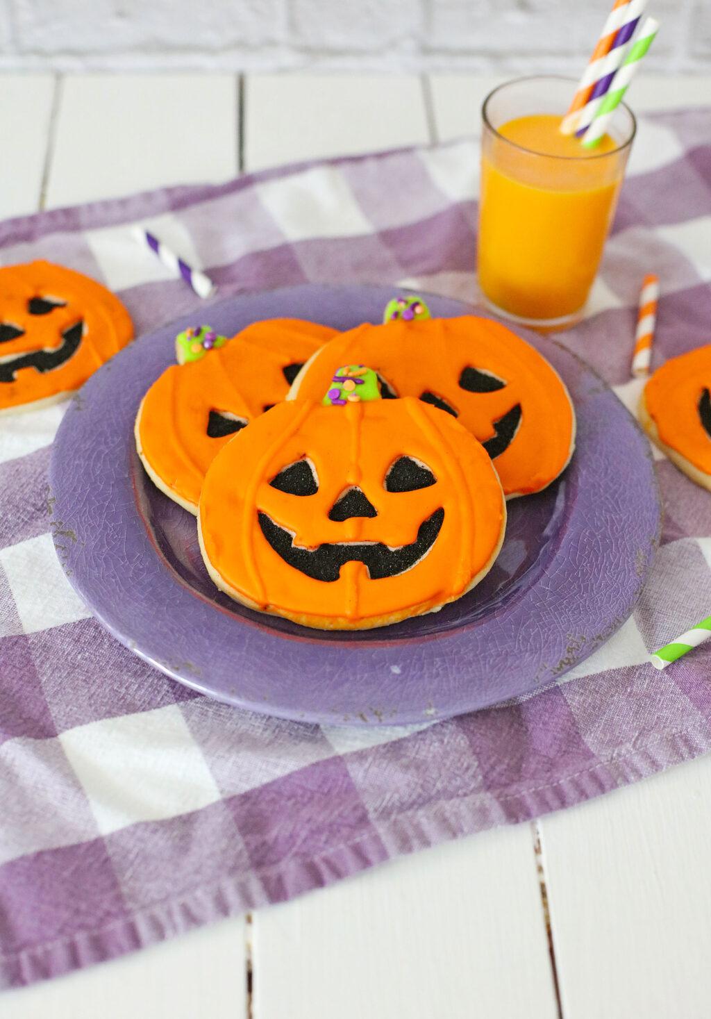 jack-o'-lantern cookies decorated to look like pumpkins on a purple plate