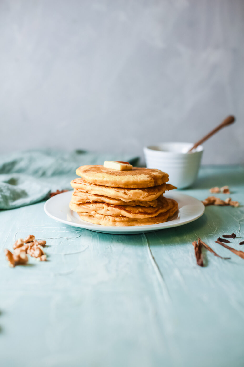 pumpkin spice pancakes stacked on a white plate