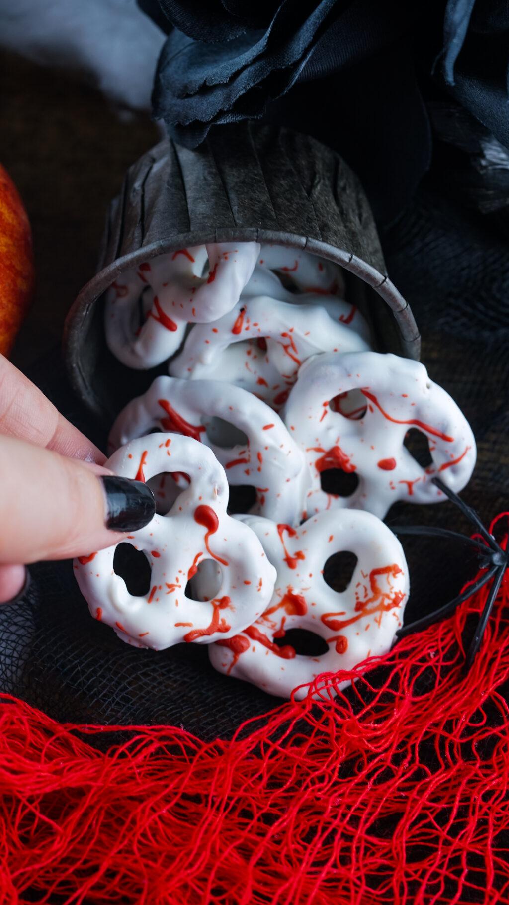 finger with black fingernail holding a bloody pretzel