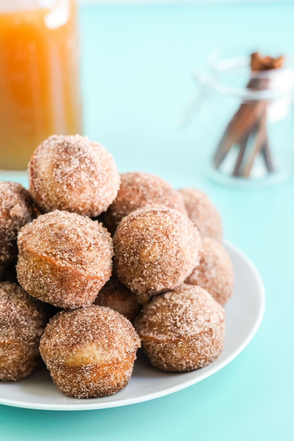 apple cider donut holes stacked on a white plate