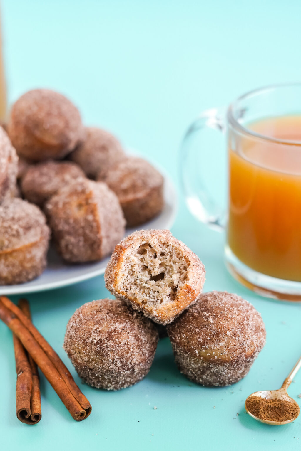 apple cider donut holes stacked on a bright blue table