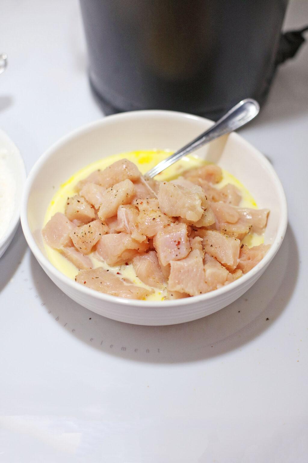 raw chicken bites in an egg mixture