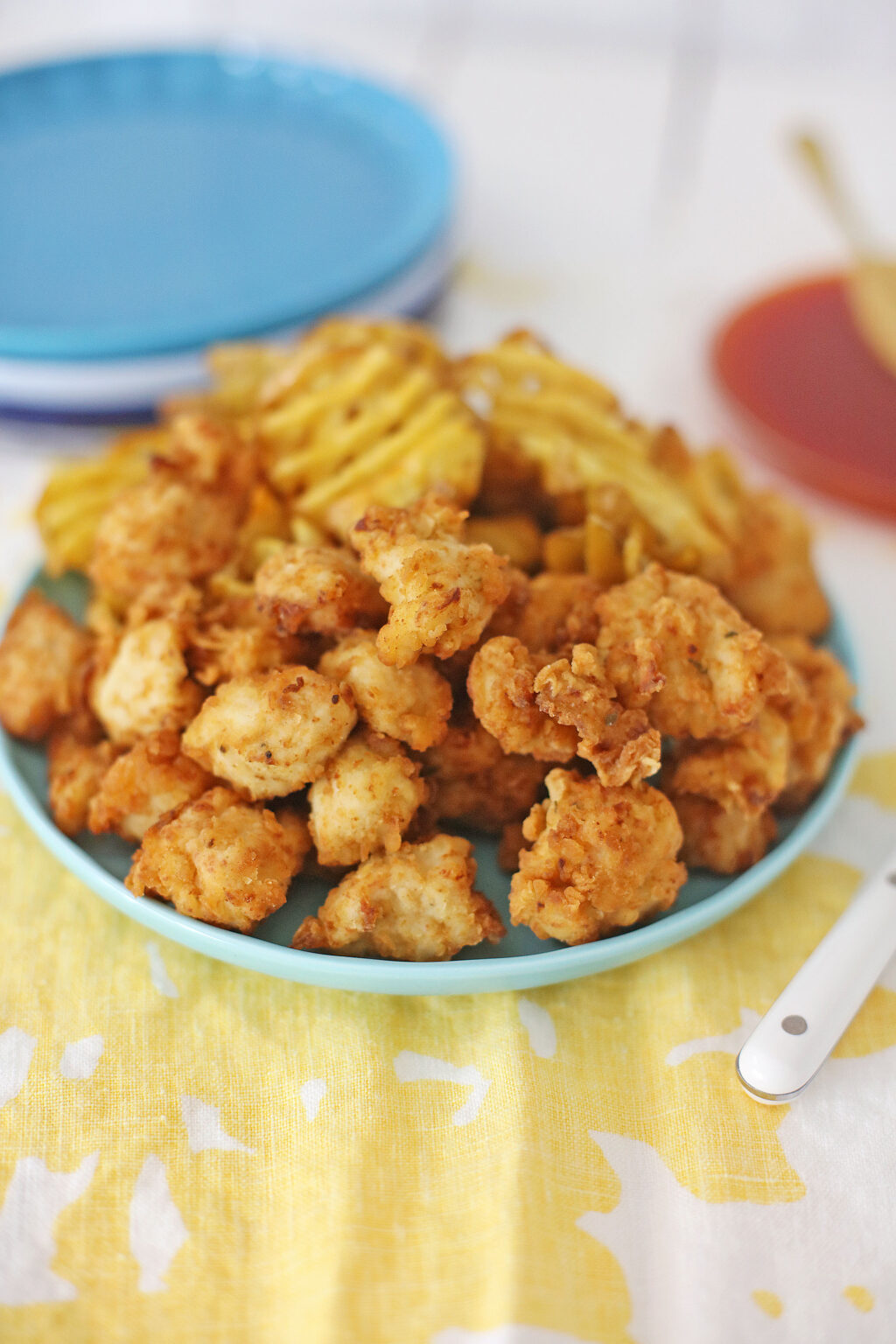 homemade chick-fil-a nuggets on a blue plate with a side of waffle fries