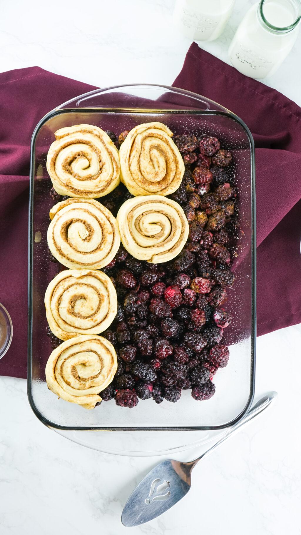 raw cinnamon rolls on top of blackberries in a baking dish
