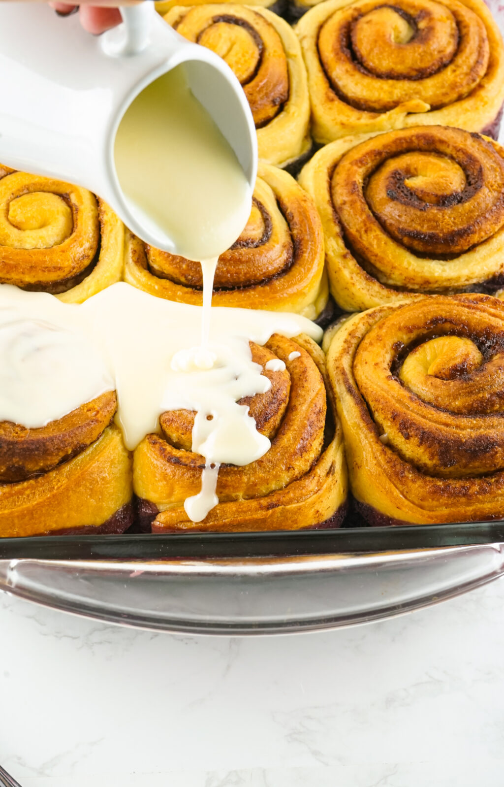 cinnamon roll frosting being poured on top of the cinnamon roll cobbler