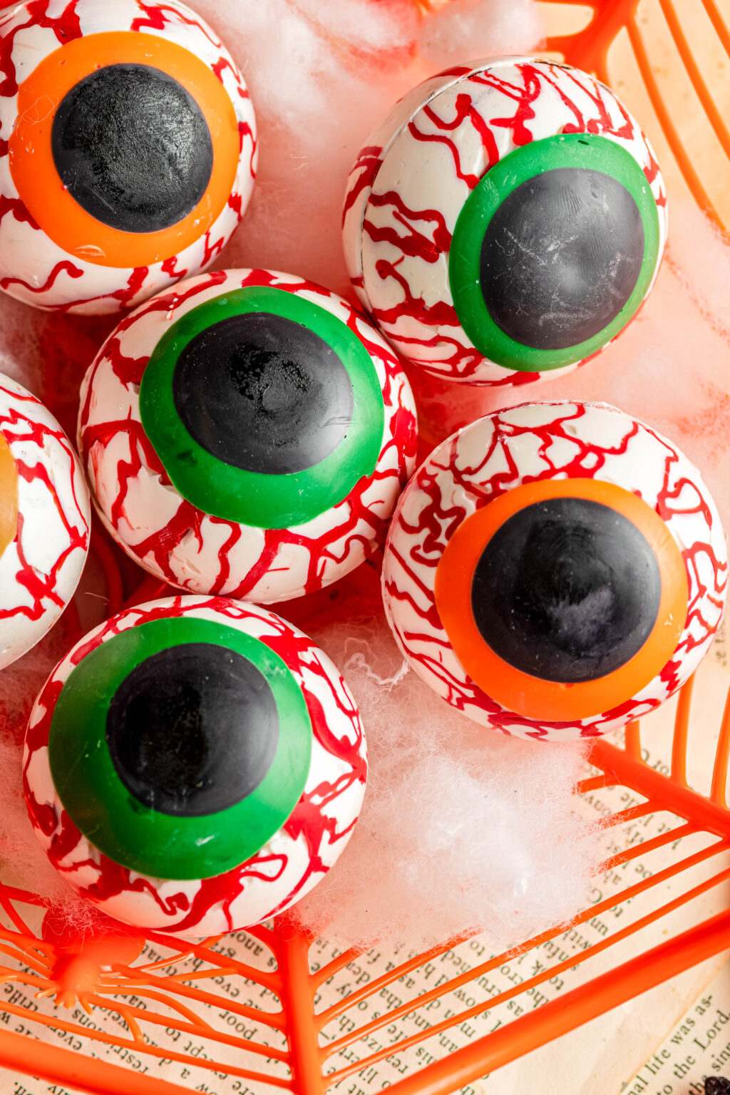 up close picture of eyeball hot cocoa bombs in an orange bowl