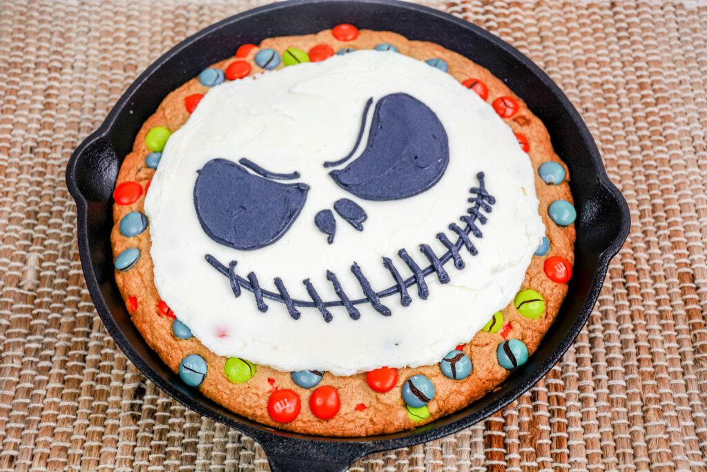 details of jack skellington face drawn in icing on top of cookie skillet