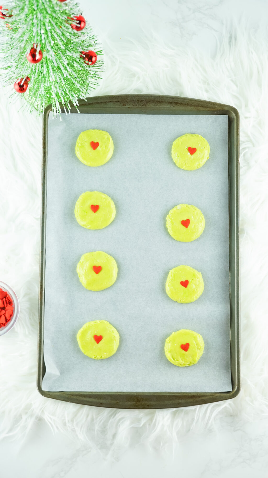 green cookie dough with red heart sprinkles on a baking sheet