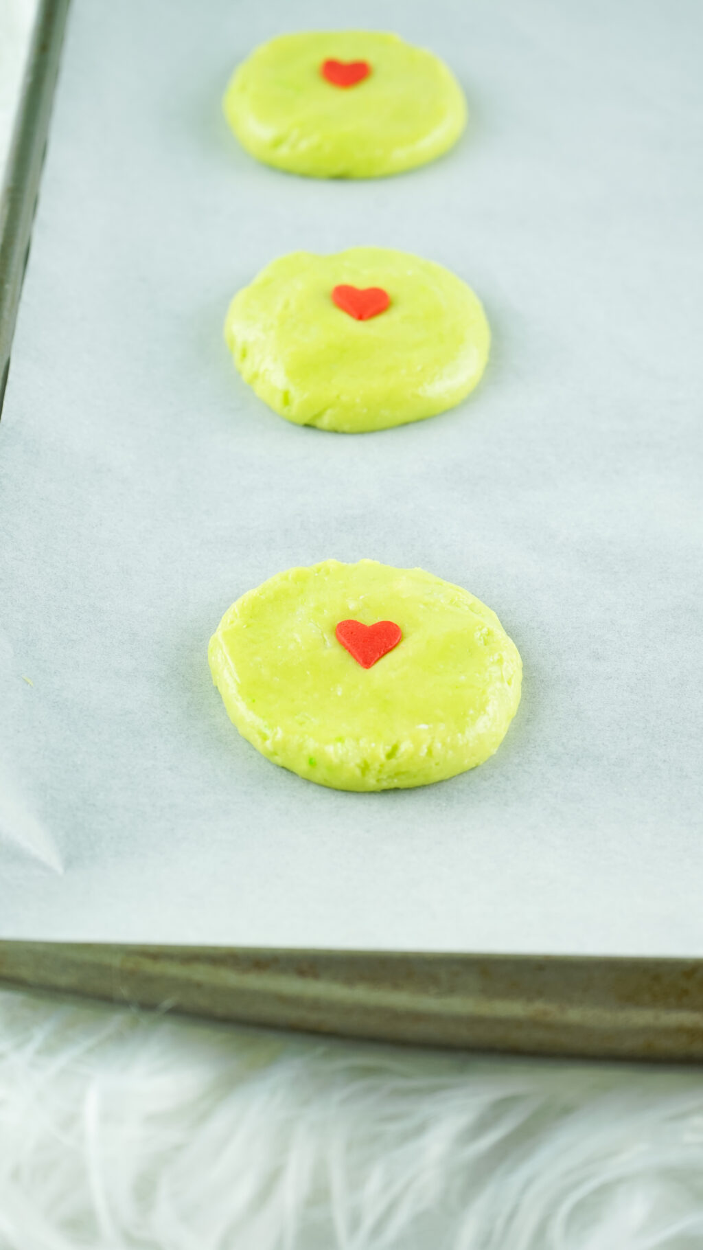 grinch cookies on a baking sheet