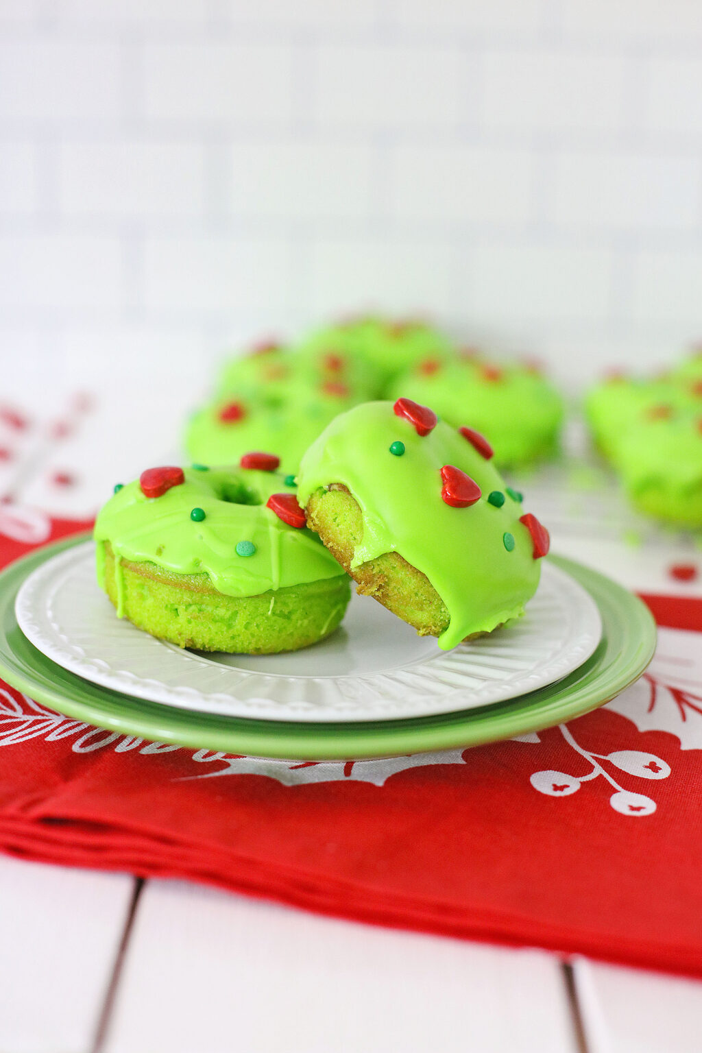 two grinch donuts side by side on a white plate
