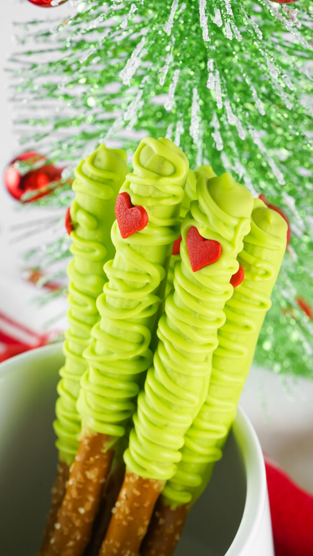 up close of grinch pretzels in a white cup